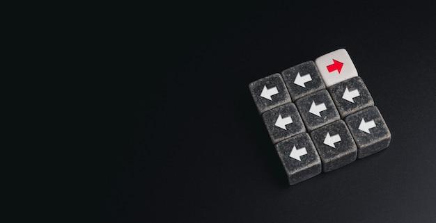 リーダーシップ、ユニーク、異なる方法の概念を考えます。コピースペース、最小限のスタイルで暗い背景に反対方向の白い矢印に面している赤い矢印のサイコロブロック。