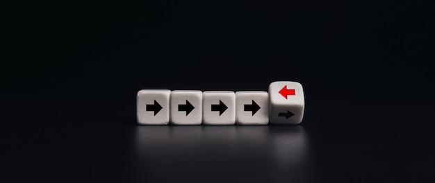 リーダーシップ、ユニーク、異なる方法の概念を考えます。白いサイコロのブロックが反転し、赤い矢印が反対方向を向いて、暗いバナーの背景に黒い矢印が表示されます。最小限のスタイルです。