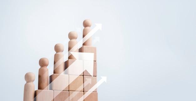 Лидерство с концепцией успеха в бизнесе. современные поднимающиеся вверх стрелки и деревянные фигуры, стоящие на шаге диаграммы графика роста, организованном деревянными кубическими блоками, изолированными на белом фоне с копией пространства.