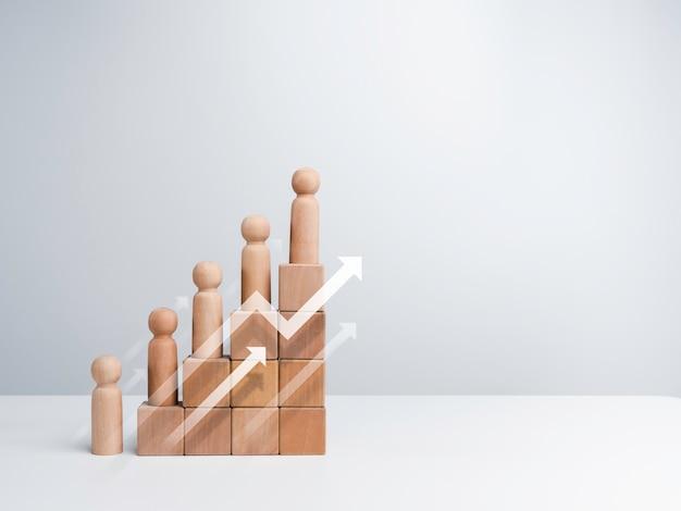 비즈니스 성공 개념을 가진 리더십입니다. 성장 그래프 차트 단계에 서 있는 현대적인 상승 화살표와 나무 그림은 복사 공간이 있는 흰색 배경에 격리된 나무 큐브 블록으로 정렬됩니다.