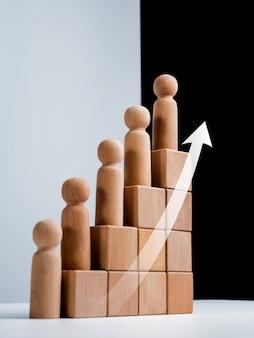 Лидерство с концепцией успеха в бизнесе. современные восходящие стрелки и деревянные фигуры, стоящие на шаге диаграммы роста, организованы деревянными кубическими блоками на белом и черном фоне, вертикальный стиль.