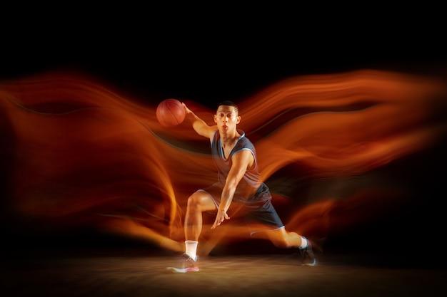Лидерство. молодой восточноазиатский баскетболист в действии и движении, прыгающий в смешанном свете на темном фоне студии. понятие спорта, движения, энергии и динамичного, здорового образа жизни.