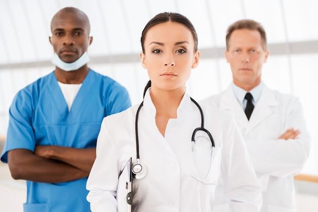 彼女のチームを率いる。彼女の同僚がバックグラウンドで彼女の後ろに立っている間クリップボードを保持し、カメラを見ている美しい女性医師