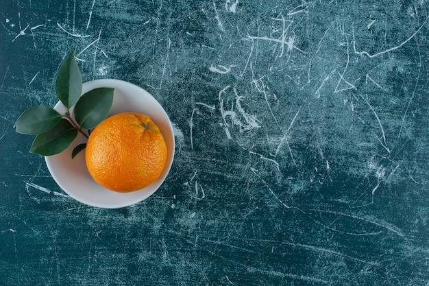 Лист и мандарин в миске на мраморном столе.