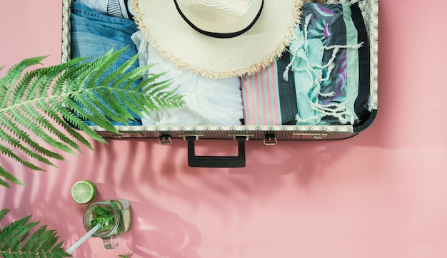 Leaf of fern, tropical detox water and open suitcase with clothes on pastel pink.