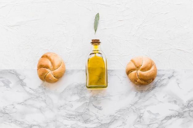 オリーブオイルボトルの上に2つの丸いパンを2つのテクスチャの背景で葉