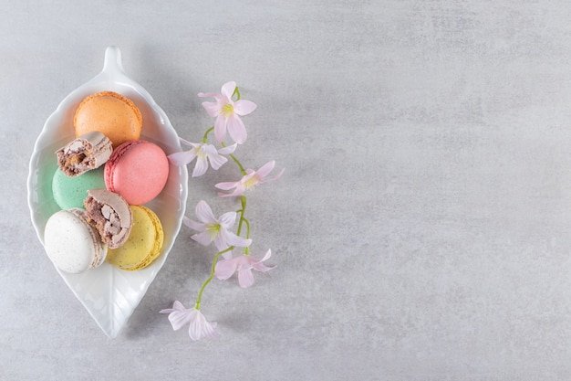 Leaf-shaped plate of colorful sweet macaroons with flowers on stone table.