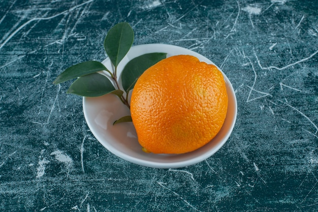 Leaf and tangerine in bowl , on the marble table.