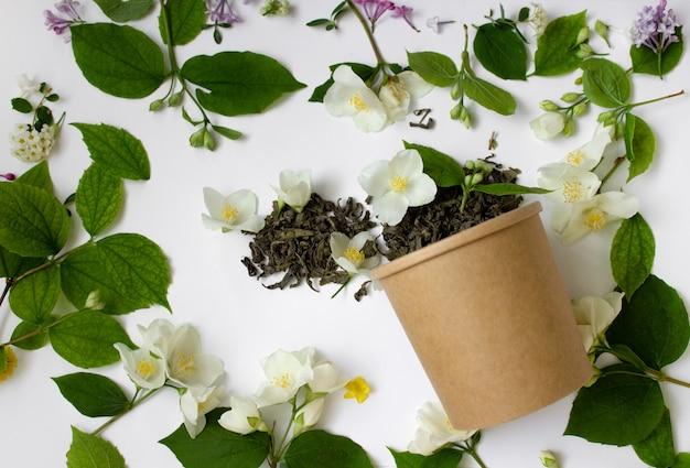 白い背景の上の丸いカートンのジャスミンと葉茶ゼロウェイストコンセプト