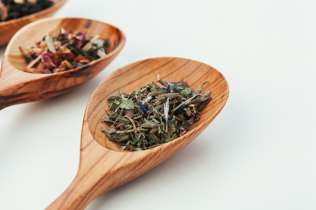 Leaf  tea in a wooden spoon isolated on white