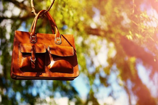 Leafesに掛かっている明るいカラフルな夏の公園でレトロな茶色の男革バッグ