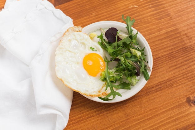Листовые овощи и наполовину жареные яйца на тарелке над деревянным столом