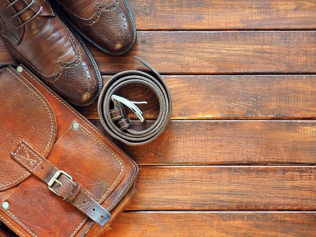 Ремень портфеля leahter и мужская обувь на деревянном фоне