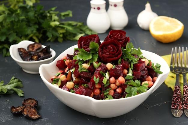白いサラダボウルにビートルートのバラで飾られた赤身のひよこ豆とビートルートのサラダ