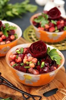 ビーツのバラで飾られた、暗い表面に対して木の板の上にある赤身のひよこ豆とビーツのサラダ