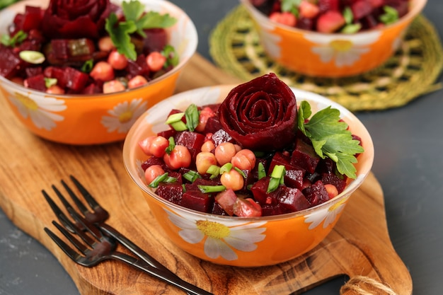 Lean chickpea and beetroot salad on a wooden board against a dark , decorated with beetroot roses