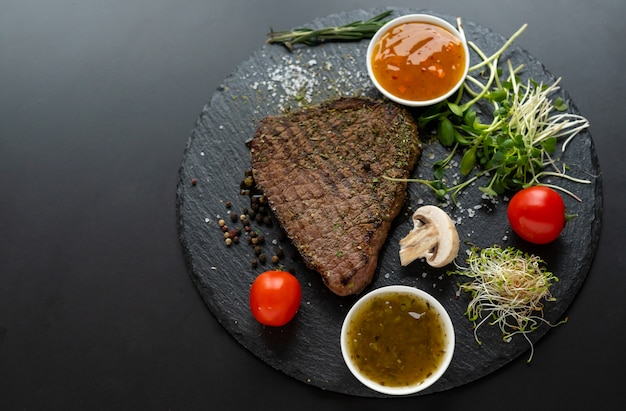 Lean grilled steak seasoned with herbs and spices served with fresh green sprouts, tomatoes and dips or dressings viewed from overhead on a round black board