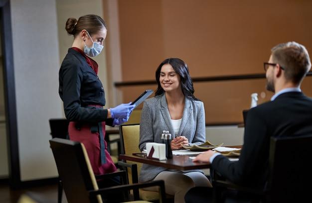 彼女のタブレットで女性の注文に関する情報を取得する赤いスカートと黒の制服を着た無駄のないウェイトレス