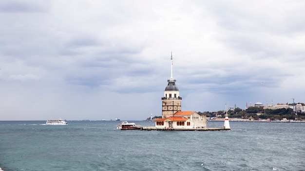 Leander's tower located on the middle of bosphorus strait, cloudy weather, moving ship and city in the distance istanbul, turkey
