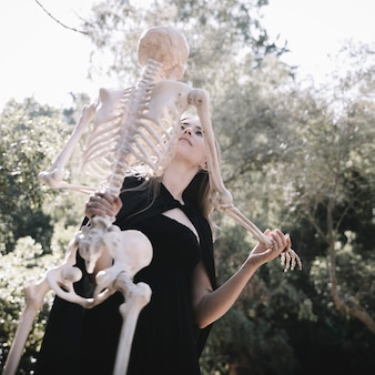 Leaning lady in witch costume holding skeleton
