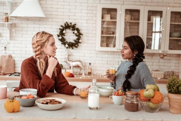 テーブルにもたれかかる。手に寄りかかって話をしながら友達の話を聞いている思いやりのある金髪の女性