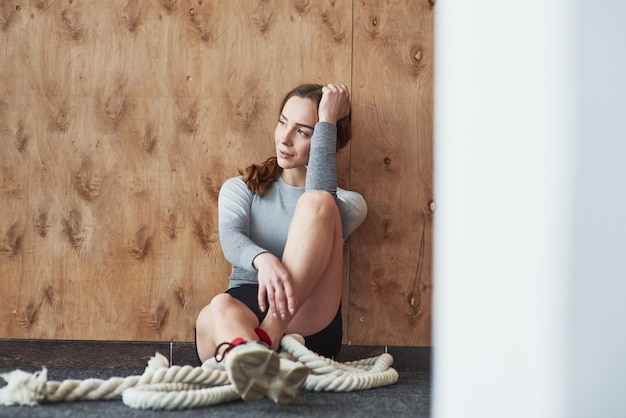 Leaning on the wooden wall. sportive young woman have fitness day in the gym at morning time