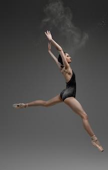 점프하는 발레리나 댄서는 회색 배경에 팔을 들고 투투를 입고 있습니다.