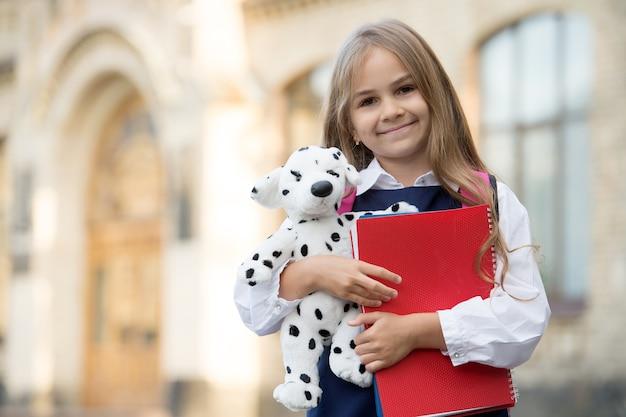 Учиться и играть счастливый ребенок держит игрушечную собаку и книги снова в школу начальное образование творчество