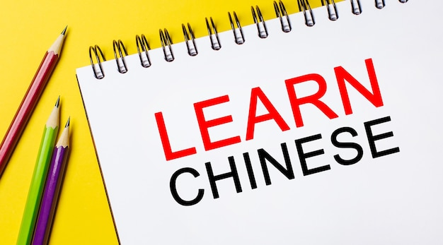Learn chinese on a white notepad with pencils on a yellow background