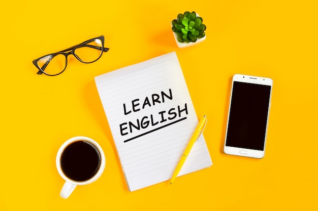 Learn english concept. notepad, mobile phone, cup of coffee, glasses