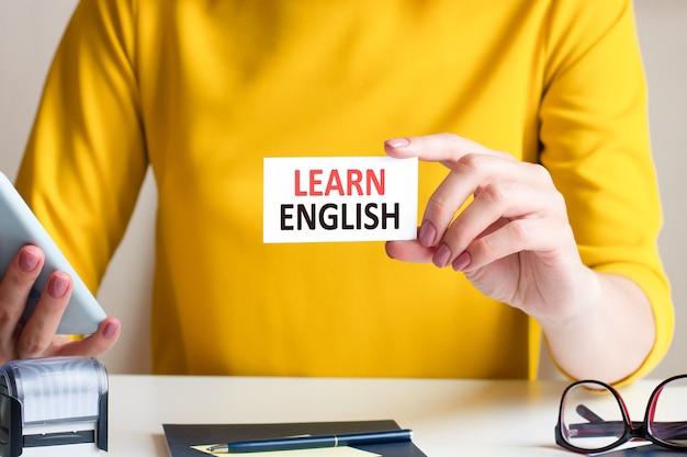 英語を学ぶは白い名刺に書かれています。女性の手は、黄色のドレスと白いノートを背景に白い紙のカードを持っています。ビジネスと広告の概念。