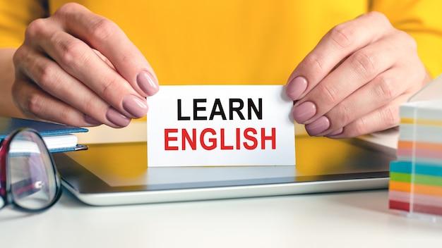 英語を学ぶは、女性の手の白い名刺に書かれています。メガネ、タブレット、メモ用のマルチカラーペーパー付きブロック。