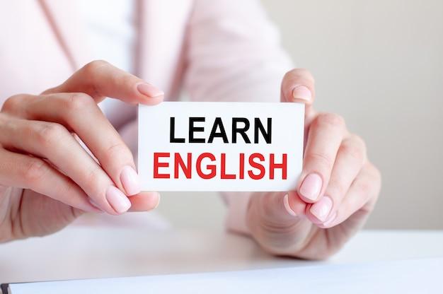 Учить английский написано на белой визитке в руках женщины. розовый фон. бизнес и рекламная концепция