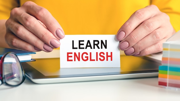 Learn english is written on a white business card in a woman's hands. glasses, tablet and block with multi-colored paper for notes.