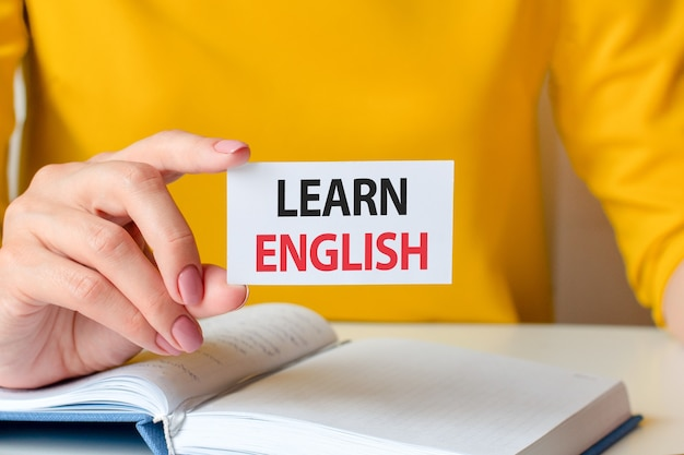Learn english is written on a white business card yellow backgrond