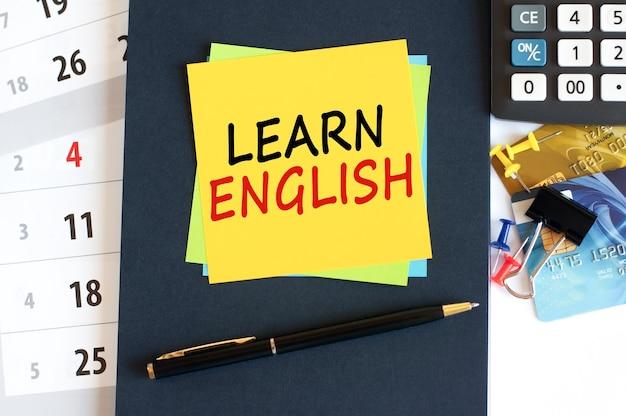 青い背景に黄色い紙の正方形の形で英語、テキストを学びます。デスクトップ上のメモ帳、電卓、クレジットカード、ペン、文房具。ビジネス、金融、教育の概念。セレクティブフォーカス。