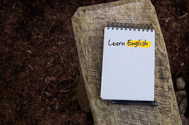 木や森のテクスチャを背景にノートページに書かれた英語のテキストを学ぶ