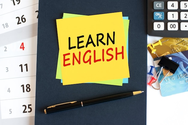 Learn english, text on yellow paper square shape on a blue background. notepad, calculator, credit cards, pen, stationery on the desktop. business, financial and education concept. selective focus.
