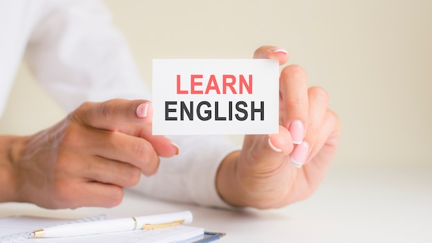 Learn english words inscription on white card paper sheet in hands of woman. black and red letters on white paper. business concept, grey backgrond