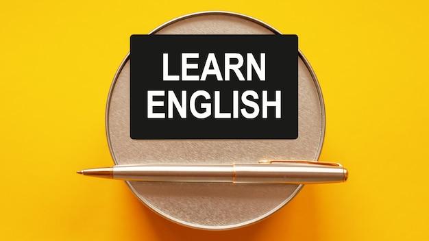 英語を学ぶ-紙に白い文字を書く言葉。丸い金属製のスタンドと金属製の筆記ペンで黄色の背景にテキストと黒のカード。ビジネスと金融の概念