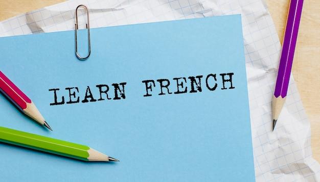 사무실에서 연필로 종이에 쓰여진 프랑스어 텍스트 배우기