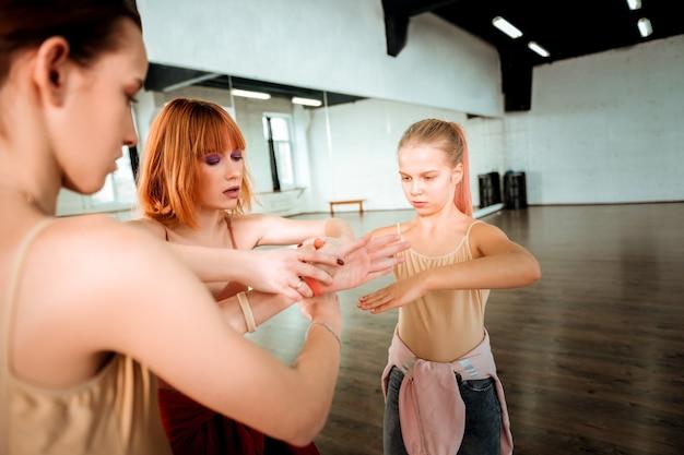 新しい動きを学びましょう。生徒たちに動きを見せながら真面目に見える赤い髪の美しいダンス教師