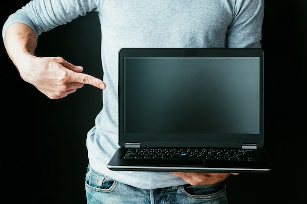 인터넷에서 새로운 직업을 배우십시오. 우리와 함께 프로그래머 코더 또는 웹 개발자가 되십시오. 빈 검은 노트북 화면을 손가락으로 가리키는 남자.