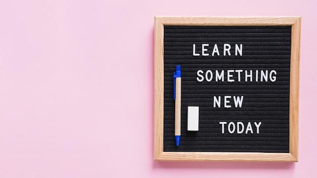 분홍색 배경 위에 펜과 지우개가있는 슬레이트에서 새로운 오늘의 텍스트를 배우십시오.