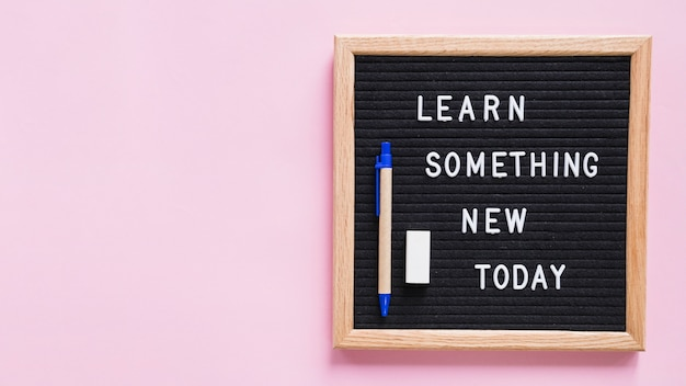 Learn something new today text on slate with pen and eraser over pink background