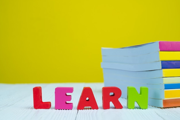 Learn text alphabet and pile of book on white table with yellow background.