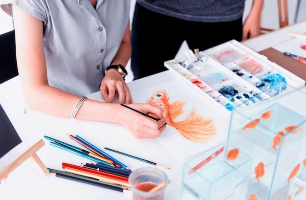물고기를 그리는 법을 배웁니다. 종이에 스케치, 페인트 및 채색.