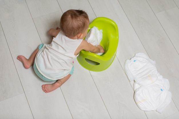 챔버 냄비를 사용하는 법을 배웁니다. 귀여운 아기가 바닥에 앉아 놀이를 하고 깨끗한 기저귀를 녹색 밤 냄비에 넣습니다.