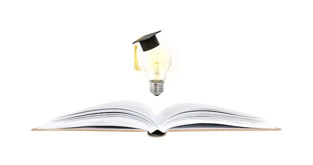 학습 및 아이디어 개념. 펼친 책 위에 대학원 모자와 빛나는 전구.