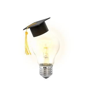 학습 및 아이디어 개념입니다. 흰색 배경에 분리된 대학원 모자가 있는 빛나는 전구.